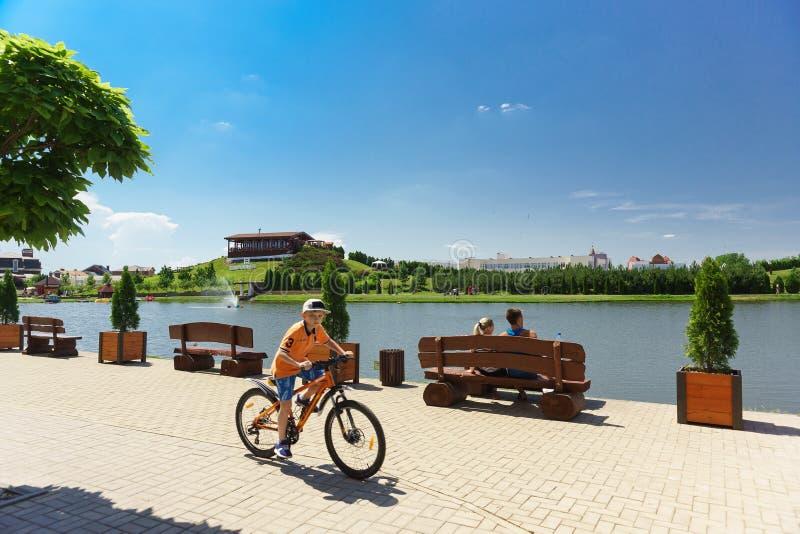 Junge reitet sein Fahrrad entlang der Seepromenade Sommerferien in der Stadt Sonniger Tag stockbild