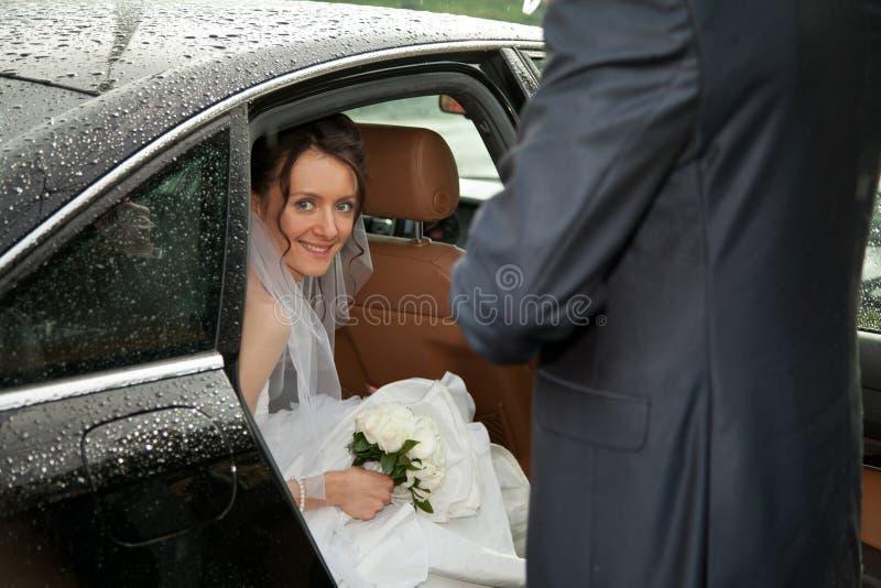 Junge reizend Braut, die aus einem Auto heraus schaut lizenzfreies stockfoto
