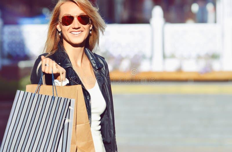 Junge reizend langhaarige Frau des Porträts, die Einkaufstaschen hält stockfotos