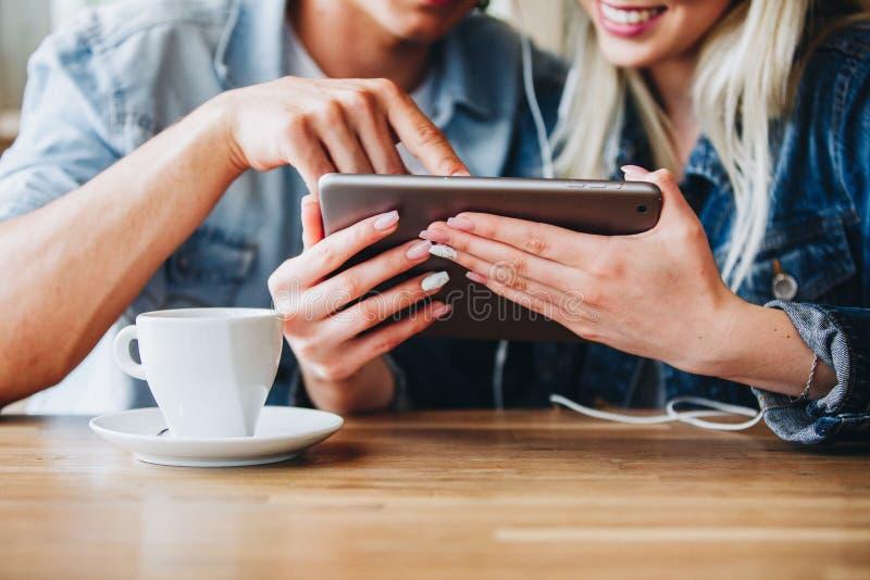 Junge reizend Paare unter Verwendung des Tablets, beim zusammen sitzen und Dr. lizenzfreies stockfoto