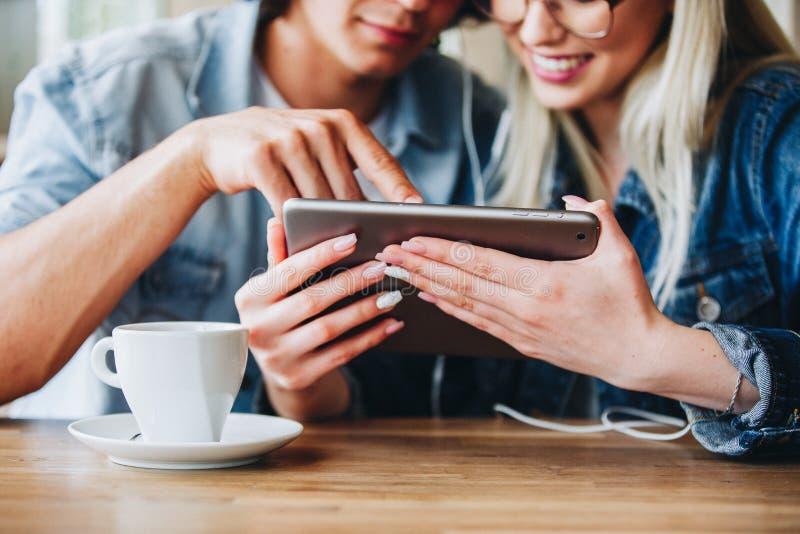 Junge reizend Paare unter Verwendung des Tablets, beim zusammen sitzen und Dr. lizenzfreie stockfotografie