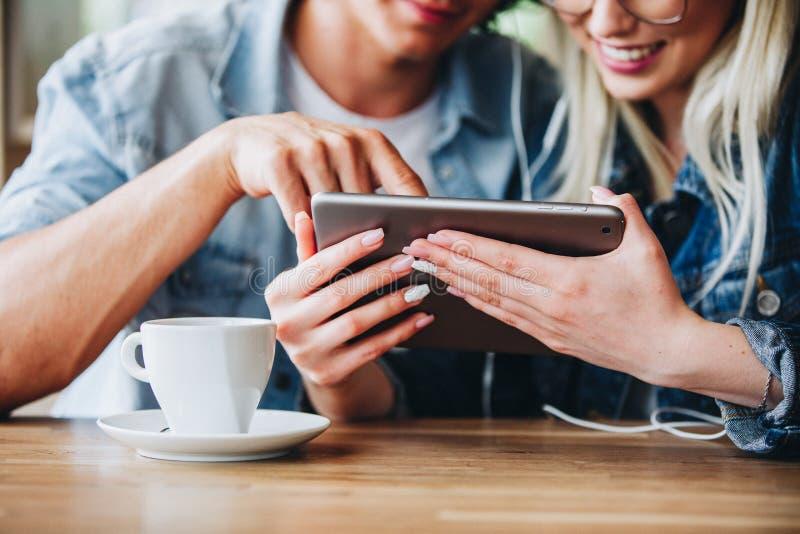 Junge reizend Paare unter Verwendung des Tablets, beim zusammen sitzen und Dr. stockbilder