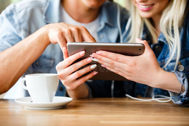 Junge reizend Paare unter Verwendung des Tablets, beim zusammen sitzen und Dr. stockbild