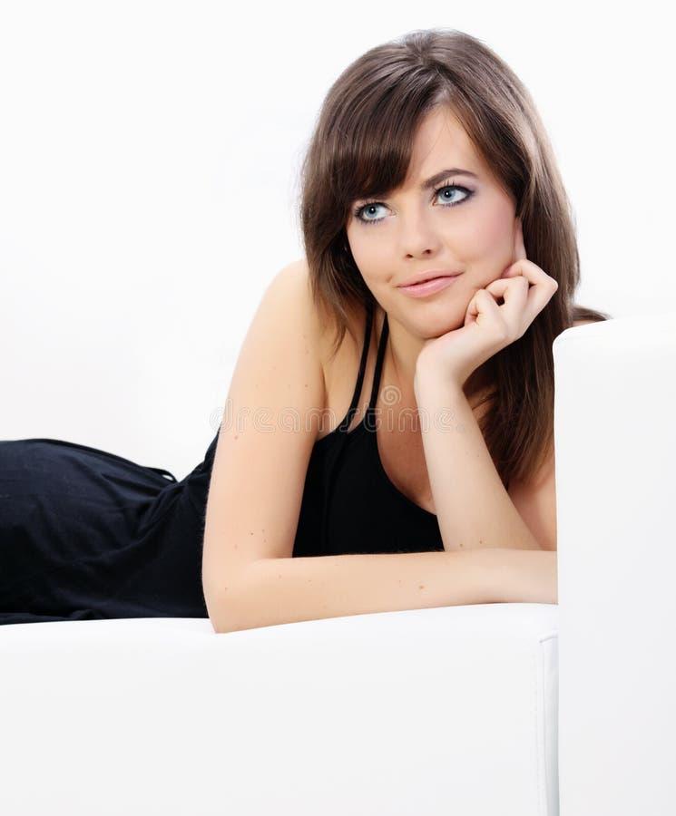Junge reizvolle Frau, die auf einem Sofa sich entspannt stockfotografie