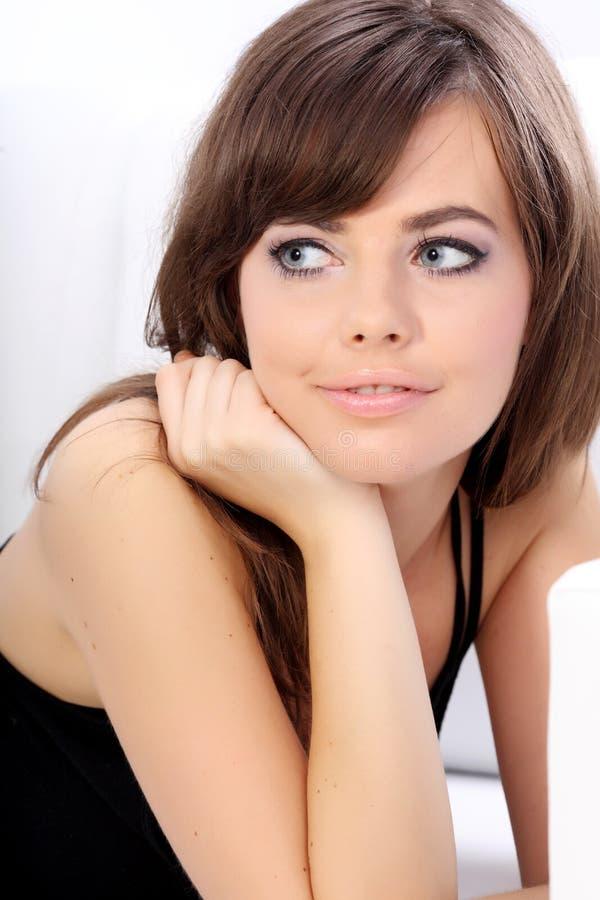 Junge reizvolle Frau, die auf einem Sofa sich entspannt stockfoto