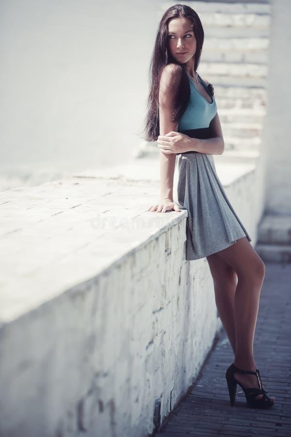 Junge reizvolle Frau, die an der Wand steht stockfotos