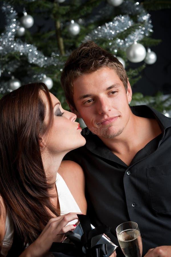 Junge reizvolle Paare vor Weihnachtsbaum stockfotografie