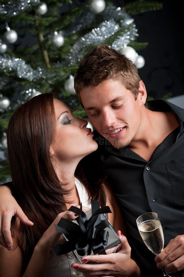 Junge reizvolle Paare vor Weihnachtsbaum lizenzfreie stockbilder