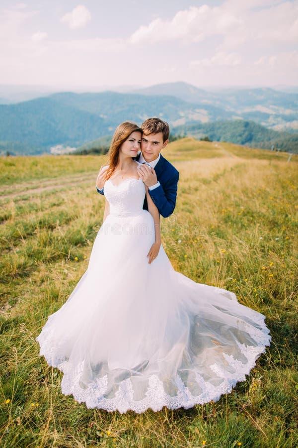 Junge romantische Heiratspaare, die auf sonniger Rasenfläche mit entferntem Forest Hills und erstaunlichem Himmel als Hintergrund lizenzfreie stockbilder