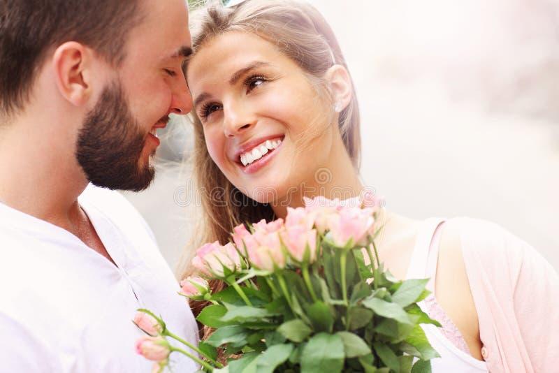 Junge romantische Paare mit Blumen lizenzfreie stockfotografie