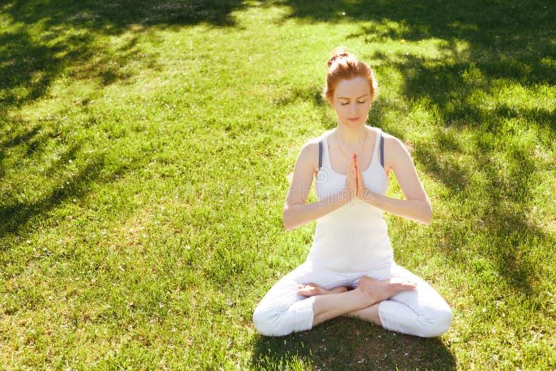 Junge rote Haarfrau, die friedlich im Park meditiert lizenzfreie stockbilder