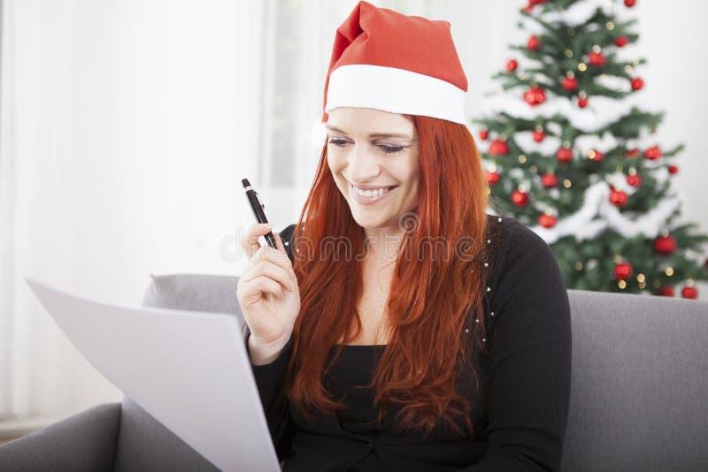 Junge rote Haarweihnachtsmädchenwunschliste lizenzfreie stockfotografie