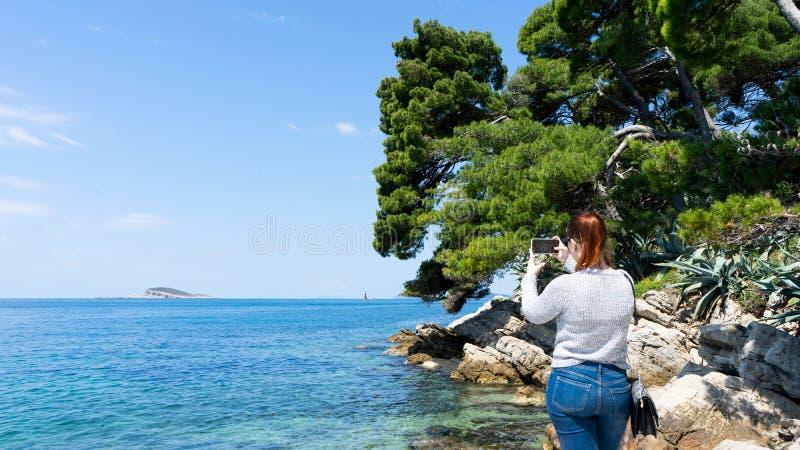 Junge rote Hauptfrau, die Foto mit intelligentem Telefon zum blauen adriatisches Seesauberen und transparenten Wasser in der Feie stockbilder