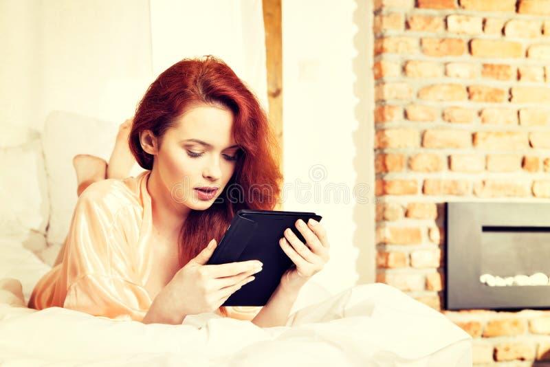 Junge rothaarige Frau, die Internet Computertablettengrasens verwendet lizenzfreies stockbild