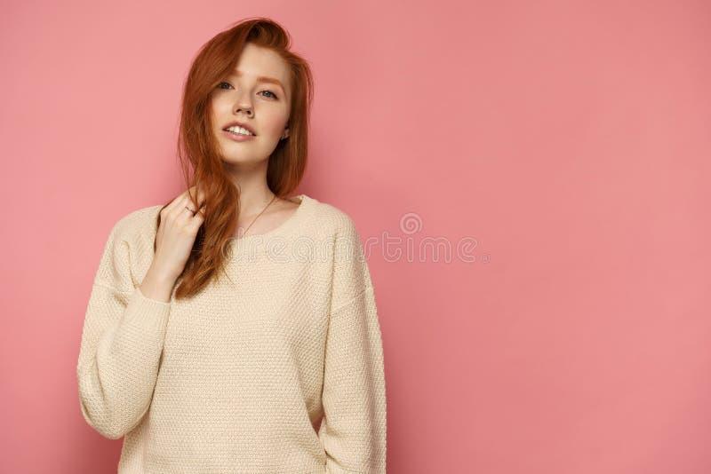 Junge Rothaarigefrau berührt ihr Haar und Blicke an der Kamera auf rosa Hintergrund lizenzfreie stockfotos