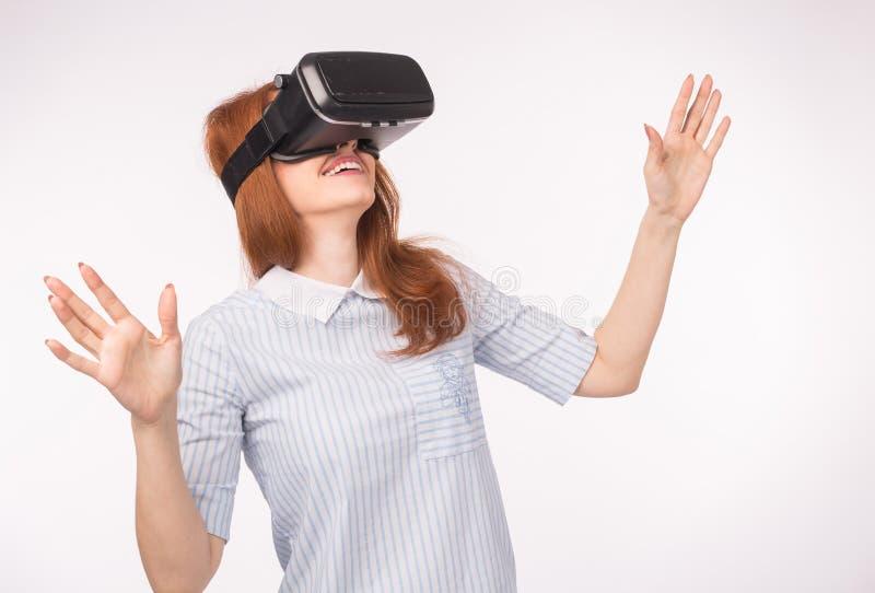 Junge Rothaarigefrau, die Gläser virtuelle Realität verwendet stockfoto