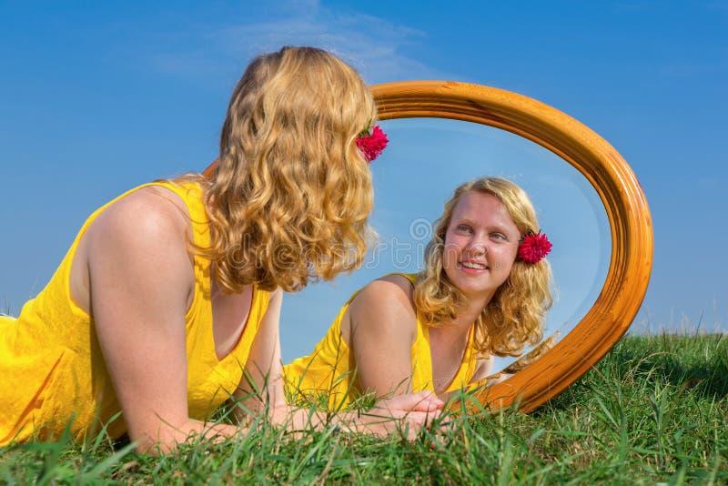 Junge Rothaarigefrau, die mit Spiegel draußen liegt stockfotografie