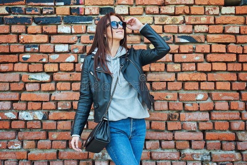 Junge Rothaarigefrau, die nahe der Backsteinmauer aufwirft stockfotografie