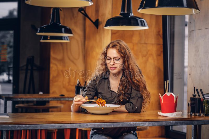 Junge Rothaarigefrau, die würzige Nudeln in einem asiatischen Restaurant isst lizenzfreie stockbilder