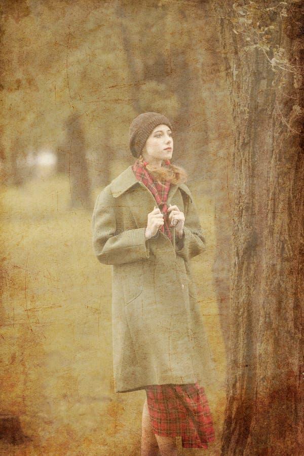 Junge Rothaarigefrau im roten Kleid mit grünem Mantel am Herbst übertreffen lizenzfreies stockbild