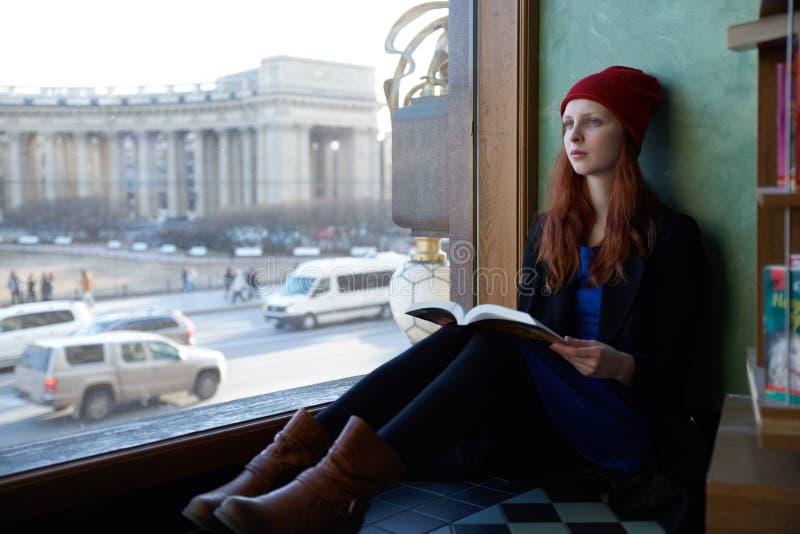 Junge Rothaarigefrauen-Studentin, die am Fenster Ablesena sitzt lizenzfreie stockfotografie