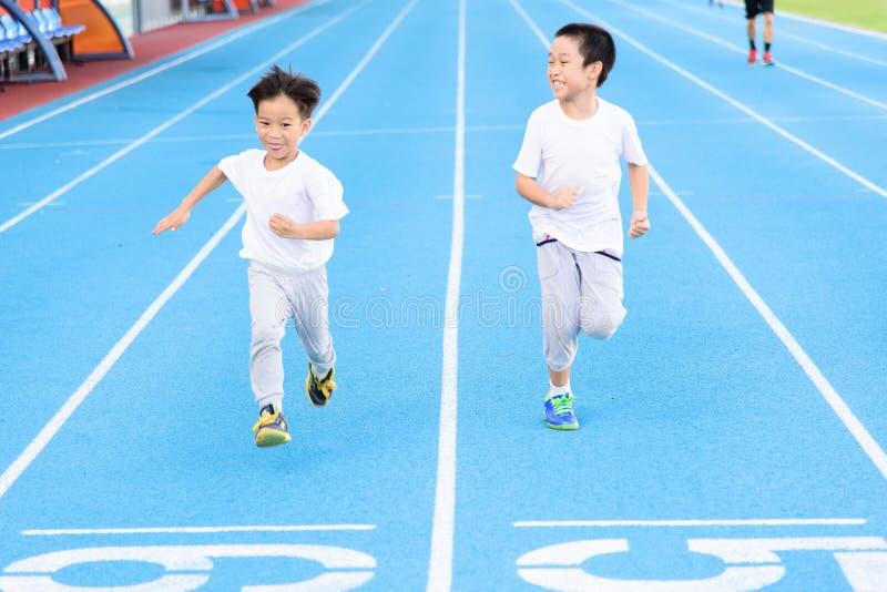 Junge runnin auf blauer Bahn stockfotos