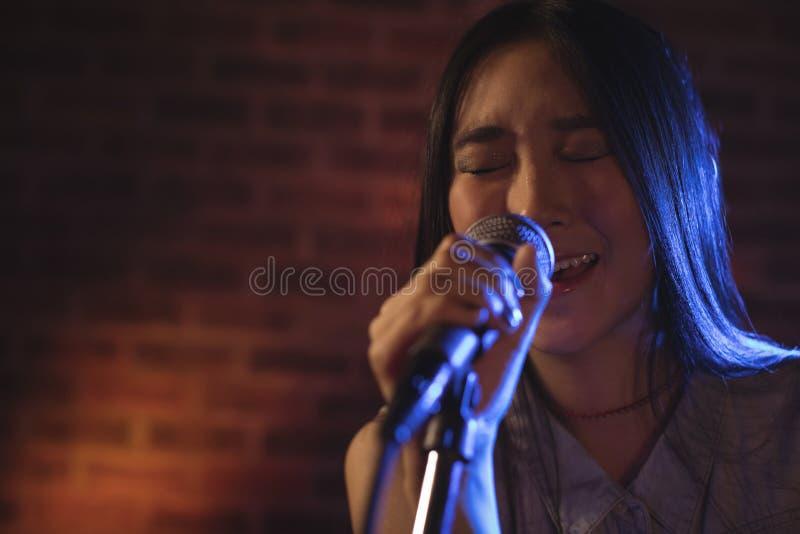 Junge Sängerin, die am Musikkonzert singt lizenzfreie stockbilder