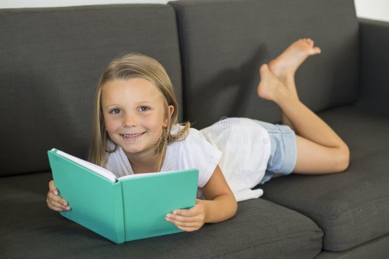 Junge süße und glückliche kleine alte Lügen des Mädchens 6 oder 7 Jahre auf der Hauptwohnzimmersofacouch, die eine Buchruhe und e lizenzfreie stockfotografie