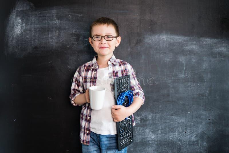 Junge ` s, das mit Tastatur stehen und Netz verdrahten nahe Tafel Junger Programmierer oder Systemverwalter Kreatives Design Co stockfotos
