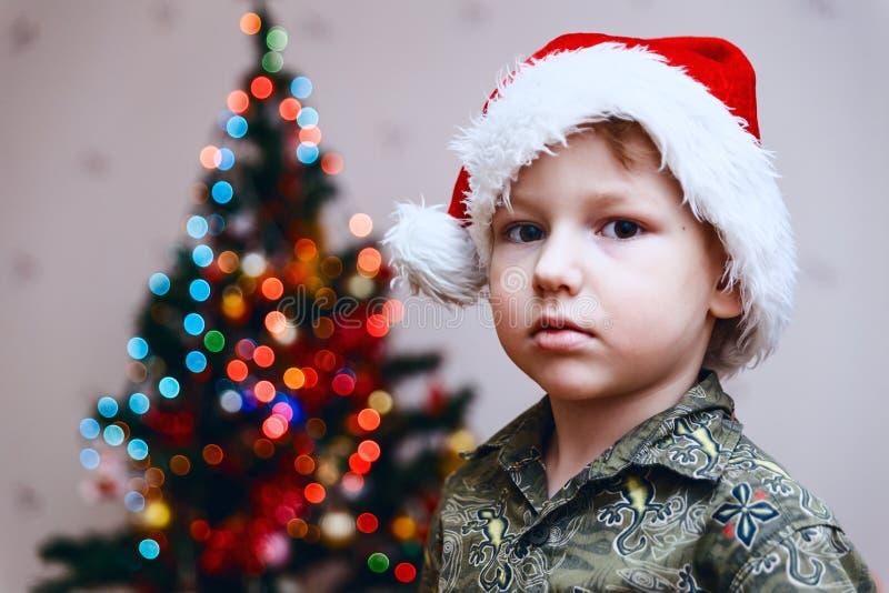 Junge in Sankt Kappe auf Weihnachtsbaumhintergrund stockbilder