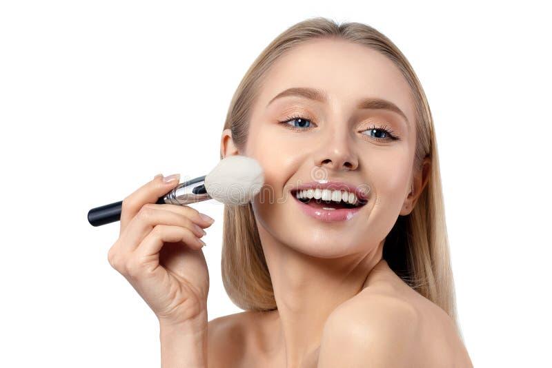 Junge schöne kaukasische Frau, die Make-up anwendet stockbild