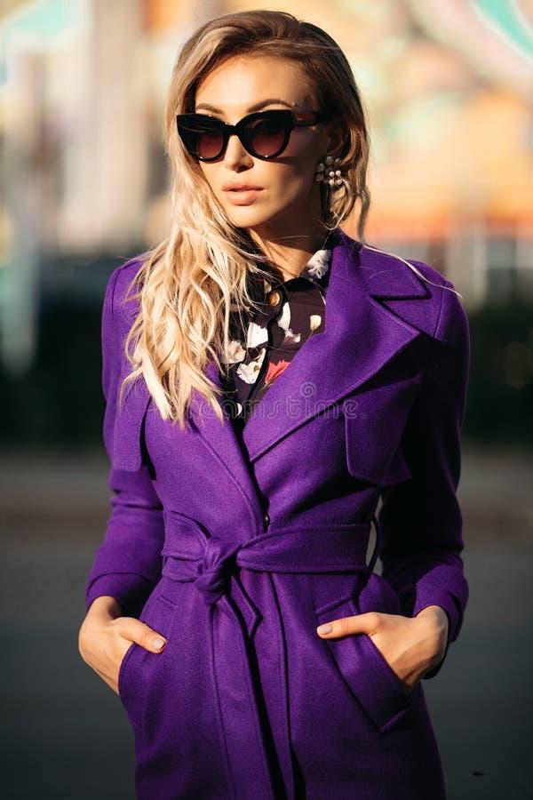 Junge schöne stilvolle Frau in der Sonnenbrille und in violettem Mantel, die an der Straße aufwerfen stockfotos