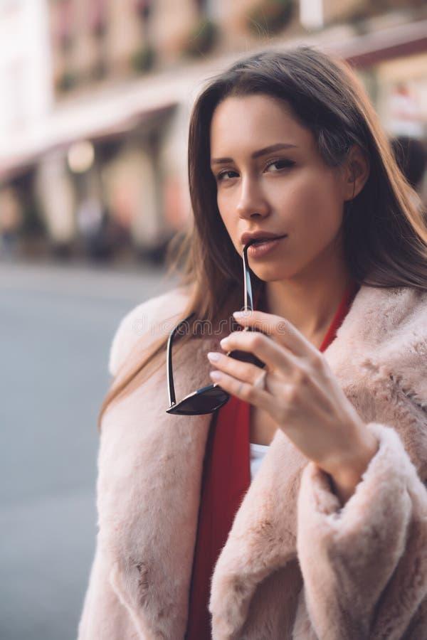 Junge schöne stilvolle Frau, die in rosa Mantel geht lizenzfreie stockfotos