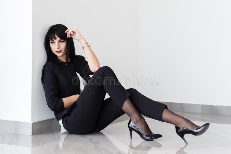 Junge schöne traurige brunette Frau gekleidet in einem schwarzen Anzug, der auf einem Boden in einem Büro sitzt stockbild