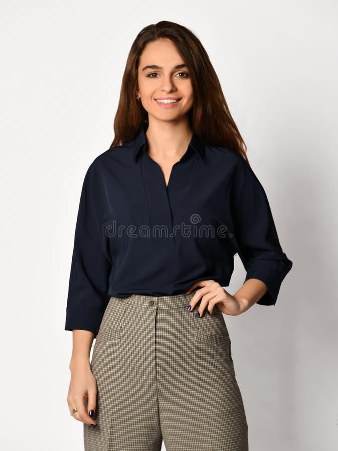 Junge Schönheit, die im glücklichen Lächeln des neuen zufälligen Bürostoffschwarz-Hemdes auf einem Weiß aufwirft lizenzfreie stockfotos