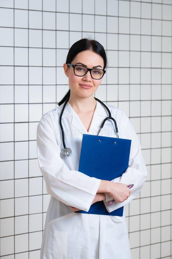 Junge schöne Ärztin im weißen chirurgischen Mantel mit schwarzem Stethoskop und blauem Papierhalter in den Händen, die an stehen stockfoto