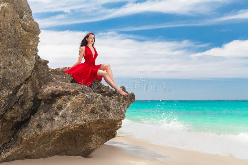 Junge schöne alleinfrau im roten Kleid, das auf dem Felsen sitzt lizenzfreies stockbild