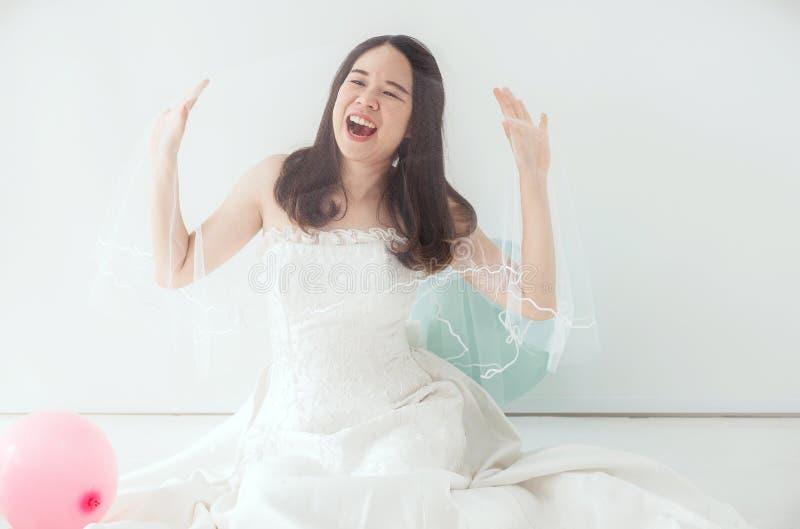 Junge schöne asiatische Brautfrau im weißen Kleid, das glücklich und mit Ballon lustig sich fühlt stockfotografie
