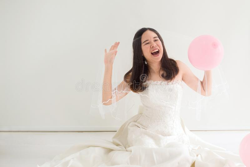 Junge schöne asiatische Brautfrauen im weißen Kleid, das glücklich und mit Ballon lustig sich fühlt stockbild