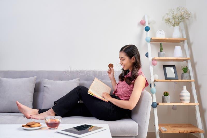 Junge schöne asiatische Frau, die auf der Couch liest ein Buch enjo sitzt stockfotografie