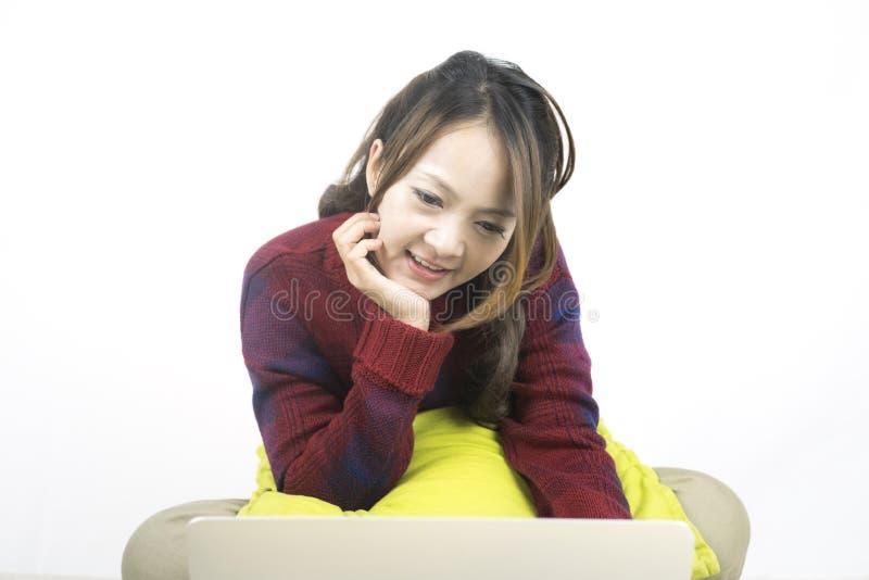 Junge schöne asiatische Frau, die Laptop-Computer verwendet stockfoto