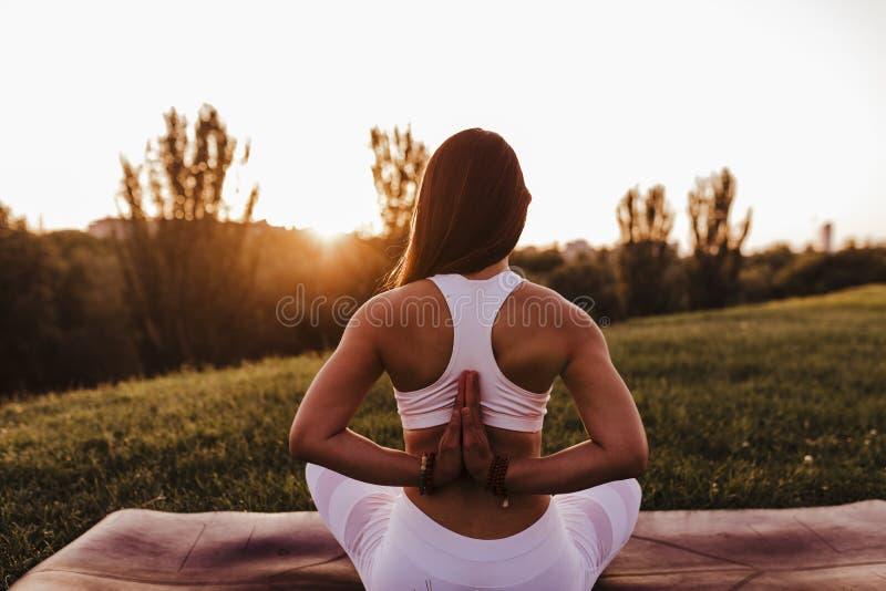 junge schöne asiatische Frau, die Yoga in einem Park bei Sonnenuntergang tut Yoga und gesundes Lebensstilkonzept R?ckseitige Ansi stockbilder