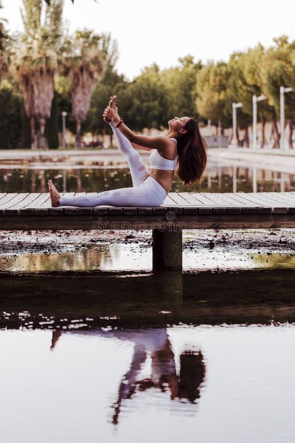 junge schöne asiatische Frau, die Yoga in einem Park tut Sitzen auf der Brücke mit Reflexion auf dem Wassersee Yoga und gesundes stockbilder