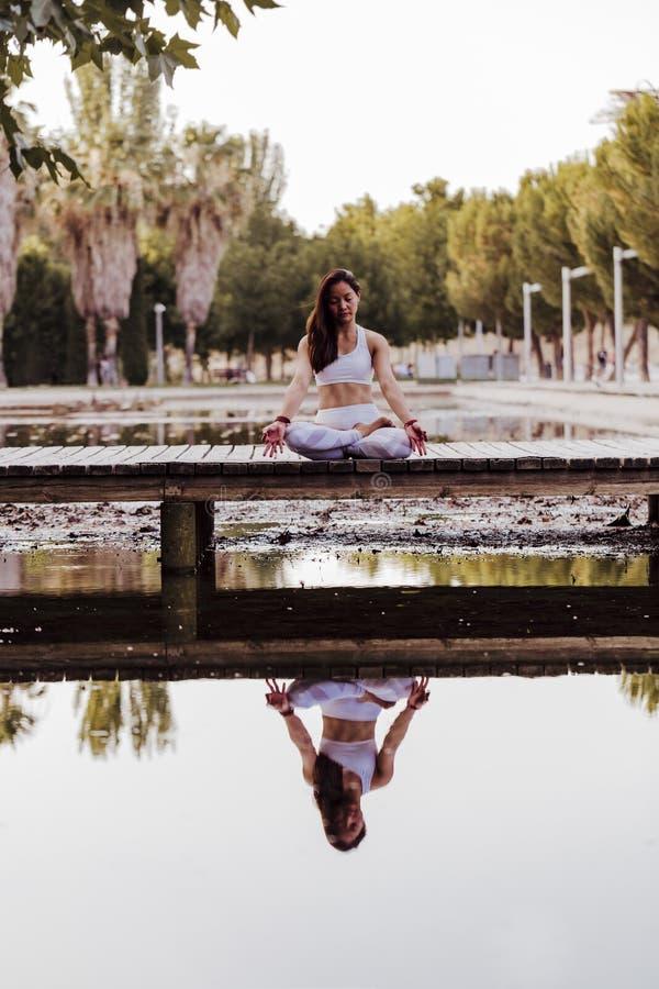junge schöne asiatische Frau, die Yoga in einem Park tut Sitzen auf der Brücke mit Reflexion auf dem Wassersee Yoga und gesundes lizenzfreies stockfoto