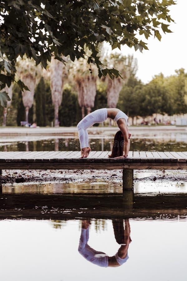 junge schöne asiatische Frau, die Yoga in einem Park tut Sitzen auf der Brücke mit Reflexion auf dem Wassersee Yoga und gesundes stockbild