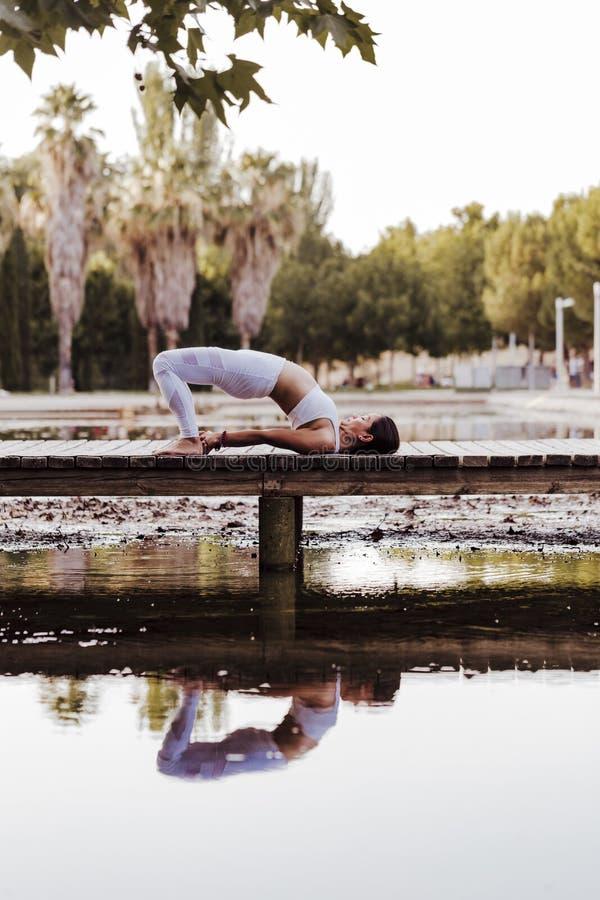 junge schöne asiatische Frau, die Yoga in einem Park tut Sitzen auf der Brücke mit Reflexion auf dem Wassersee Yoga und gesundes lizenzfreie stockbilder