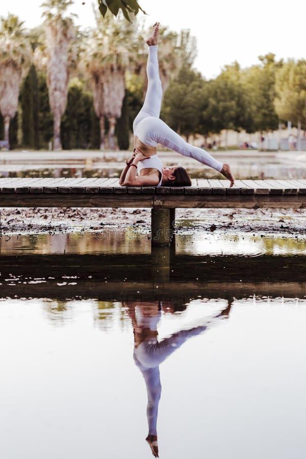 junge schöne asiatische Frau, die Yoga in einem Park tut Sitzen auf der Brücke mit Reflexion auf dem Wassersee Yoga und gesundes lizenzfreies stockbild