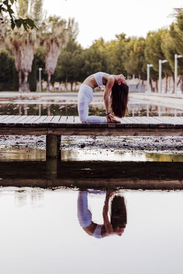 junge schöne asiatische Frau, die Yoga in einem Park tut Sitzen auf der Brücke mit Reflexion auf dem Wassersee Yoga und gesundes stockfotografie