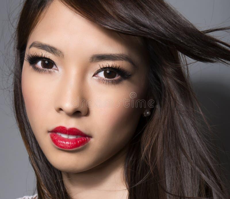 Junge schöne asiatische Frau mit makelloser Haut und dem perfekten Make-up und Braunemhaar stockfotografie