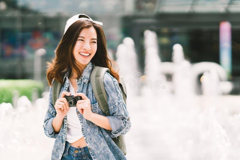 Junge schöne asiatische Rucksackreisendfrau, die digitale Kompaktkamera und das Lächeln, Kopienraum betrachtend verwendet lizenzfreie stockbilder
